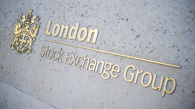 Raised brass letters form a sign for the London Stock Exchange on a concrete wall background.