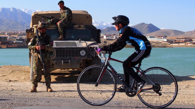 A cyclist riding past troops in Afghanistan