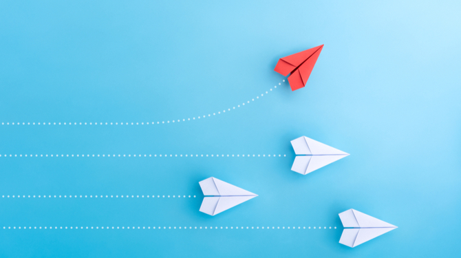 Group of paper planes in one direction and with one individual pointing in the different way