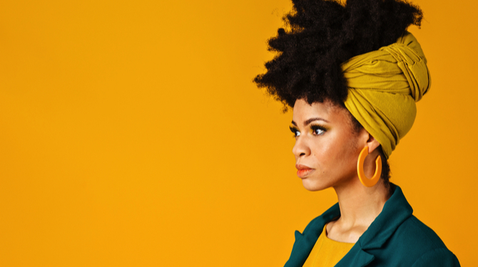 Profile portrait of a serious young woman with big yellow earrings and afro hair wrapped with head wrap scarf