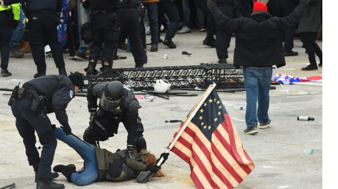 Police detain a person as supporters of US President Donald Trump protest outside the US Capitol on January 6